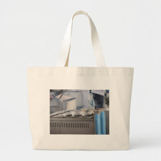 Grilling fish outdoors with smoke emerging large tote bag