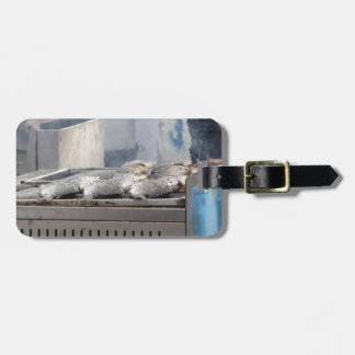 Grilling fish outdoors with smoke emerging luggage tag