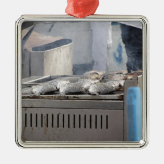 Grilling fish outdoors with smoke emerging metal ornament