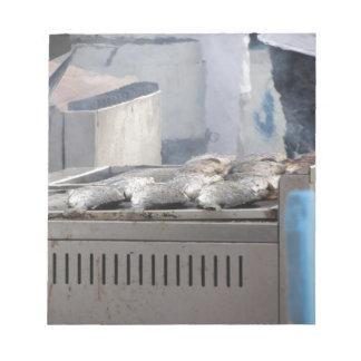 Grilling fish outdoors with smoke emerging notepad