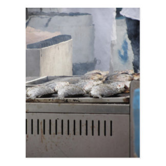 Grilling fish outdoors with smoke emerging postcard