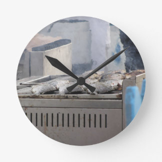 Grilling fish outdoors with smoke emerging round clock