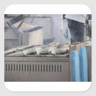 Grilling fish outdoors with smoke emerging square sticker