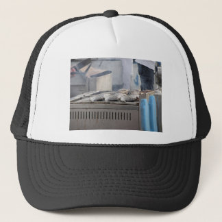Grilling fish outdoors with smoke emerging trucker hat