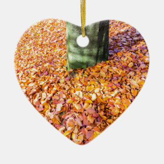 Ground around tree trunk covered with autumn leave ceramic heart ornament