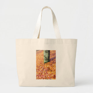 Ground around tree trunk covered with autumn leave large tote bag