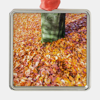 Ground around tree trunk covered with autumn leave Silver-Colored square ornament