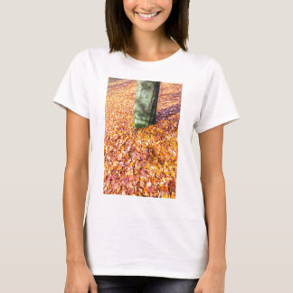 Ground around tree trunk covered with autumn leave T-Shirt