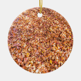 Ground covered with beech tree leaves in autumn round ceramic ornament