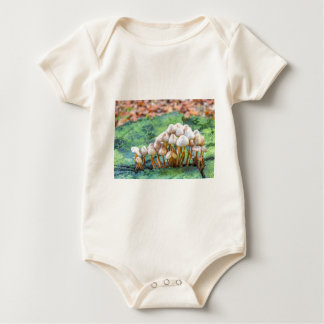 Group of mushrooms on green tree stump baby bodysuit