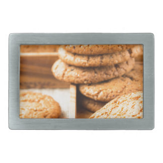 Group of oatmeal cookies on the wooden tray belt buckle