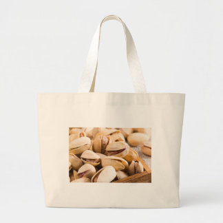 Group of salted pistachios in a small wooden box large tote bag