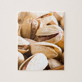 Group of salted pistachios in a small wooden box puzzles
