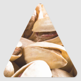 Group of salted pistachios in a small wooden box triangle sticker