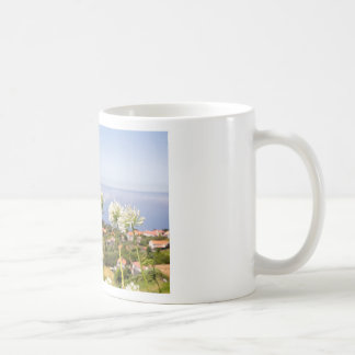 Group of white agapanthus near village and sea coffee mug