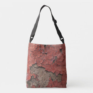Grungy peeling chipped red paint against concrete crossbody bag