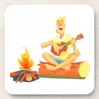 Guy Playing Guitar Sitting On A Log Next Coaster
