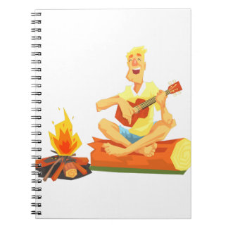 Guy Playing Guitar Sitting On A Log Next Notebook