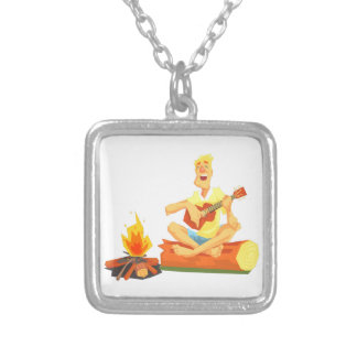 Guy Playing Guitar Sitting On A Log Next Silver Plated Necklace