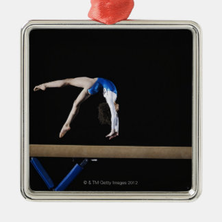 Gymnast (9-10) flipping on balance beam, side metal ornament