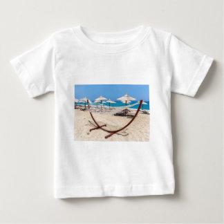 Hammock with beach umbrellas at coast baby T-Shirt