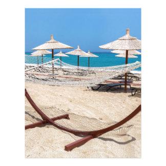 Hammock with beach umbrellas at coast letterhead