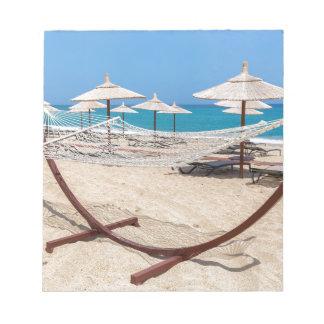 Hammock with beach umbrellas at coast notepad