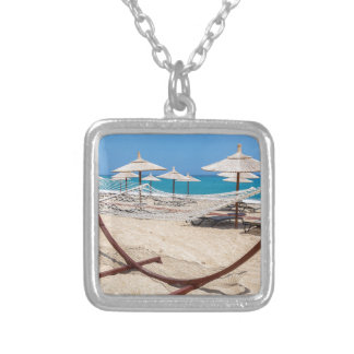 Hammock with beach umbrellas at coast silver plated necklace