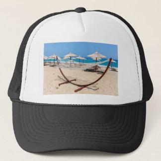 Hammock with beach umbrellas at coast trucker hat