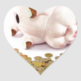 Hand counting euro coins from piggy bank heart sticker
