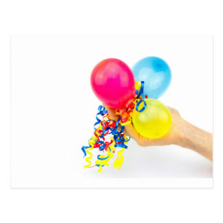 Hand giving colorful balloons with ribbons postcard