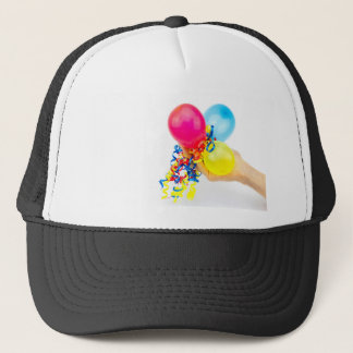 Hand giving colorful balloons with ribbons trucker hat