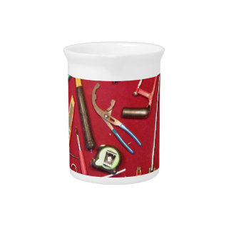 Hand held tools and tool bag red background beverage pitchers