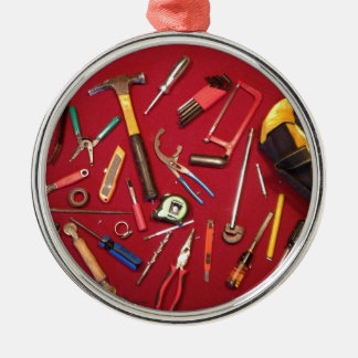 Hand held tools and tool bag red background metal ornament