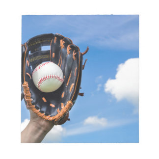 Hand holding baseball in glove with blue sky notepads