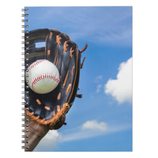 Hand holding baseball in glove with blue sky spiral notebook