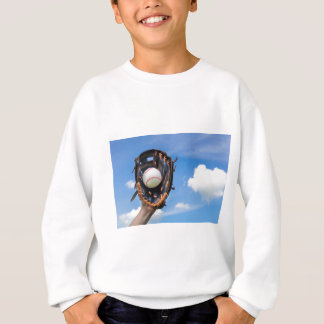 Hand holding baseball in glove with blue sky sweatshirt