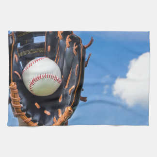 Hand holding baseball in glove with blue sky towels