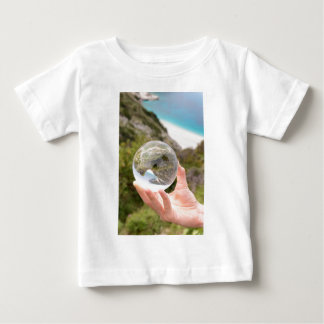 Hand holding crystal ball near sea and mountain baby T-Shirt