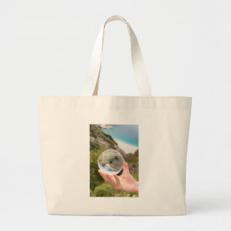Hand holding crystal ball near sea and mountain large tote bag