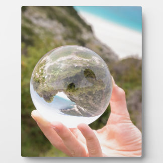 Hand holding crystal ball near sea and mountain plaque