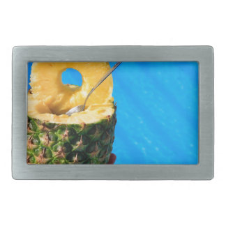 Hand holding fresh pineapple above swimming pool belt buckles