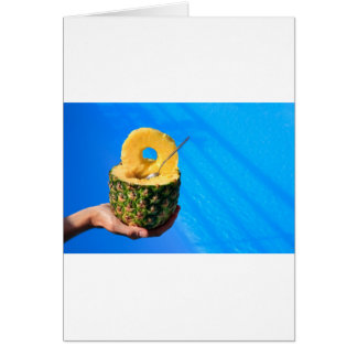 Hand holding fresh pineapple above swimming pool card