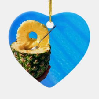 Hand holding fresh pineapple above swimming pool ceramic heart ornament