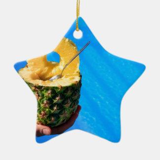 Hand holding fresh pineapple above swimming pool ceramic star ornament