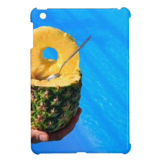 Hand holding fresh pineapple above swimming pool cover for the iPad mini