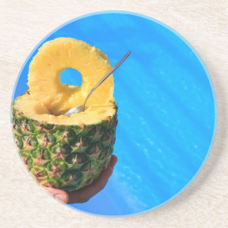 Hand holding fresh pineapple above swimming pool drink coaster