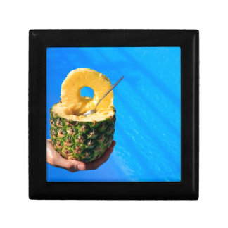 Hand holding fresh pineapple above swimming pool gift box
