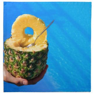 Hand holding fresh pineapple above swimming pool napkin
