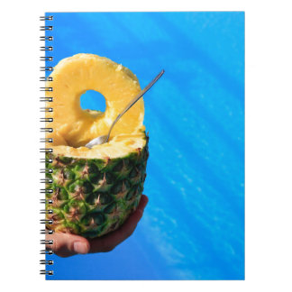 Hand holding fresh pineapple above swimming pool notebook